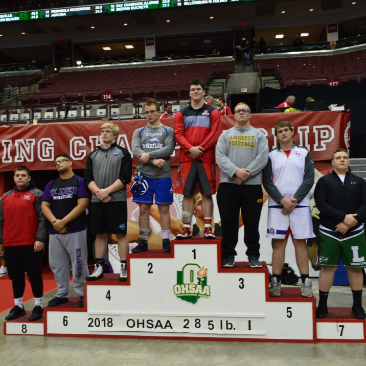 Earnest stands on the podium as he is recognized as the State Champion.